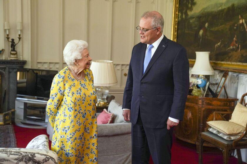 Britain's Queen Elizabeth II, left receives Australian Prime Minister Scott Morrison during an audience in the Oak Room at Windsor Castle, in Windsor, England, Tuesday June 15, 2021. (Steve Parsons/Pool Photo via AP)