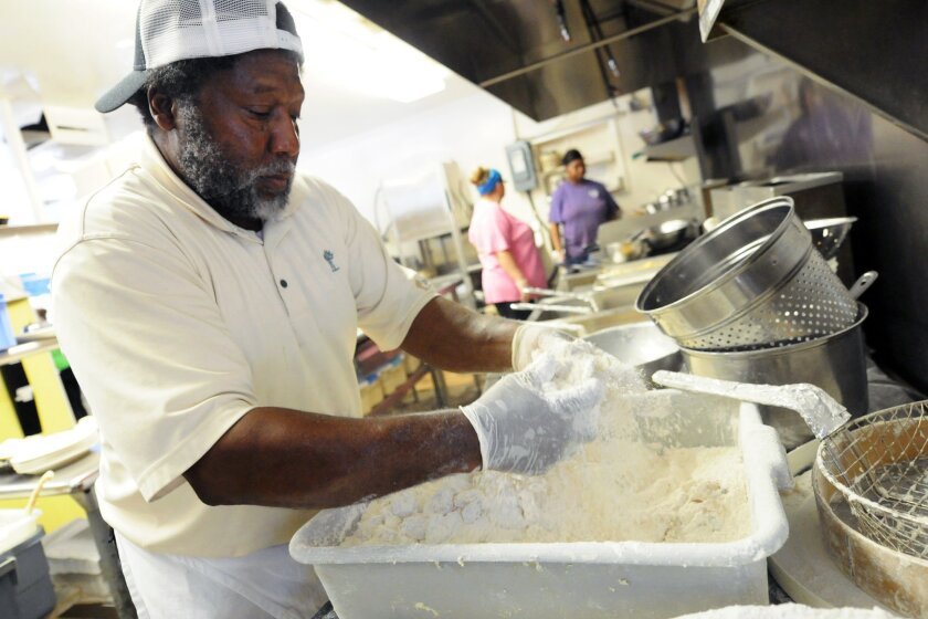 In this Sept. 17, 2014 photo, Andy Gause breads shrimp in the kitchen of the Calabash Seafood Hut in Calabash, N.C. The Institute for Supply Management releases its service sector index for September on Friday, Oct. 3, 2014. (AP Photo/The Star-News, Matt Born) LOCAL TELEVISION OUT; LOCAL INTERNET OUT
