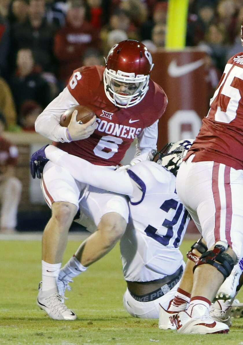 Oklahoma quarterback Baker Mayfield (6) is tackled by TCU safety Ridwan Issahaku (31) during the first quarter of an NCAA college football game in Norman, Okla., Saturday, Nov. 21, 2015. (AP Photo/Alonzo Adams)
