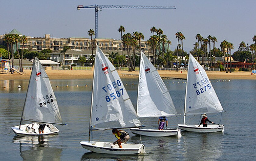 A flotilla of small sailboats float past Mother's Beach and the construction of an apartment complex in Marina del Rey July 14, 2008.