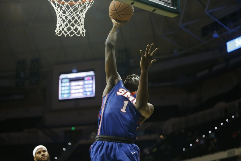 SMU guard Shake Milton (1) goes up for two points as South Florida center Jaleel Cousins, left, looks on during the first half of an NCAA college basketball game on Sunday, Feb. 7, 2016, in Tampa, Fla. (AP Photo/Brian Blanco)