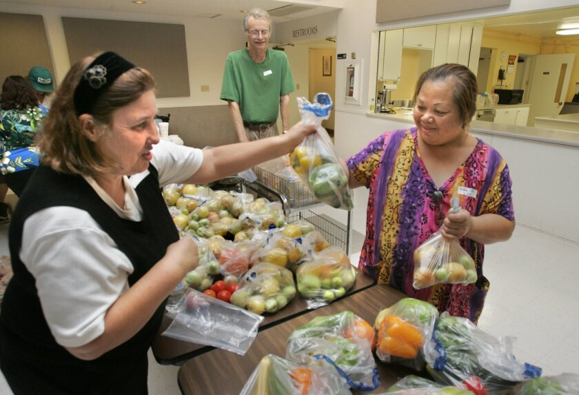 Ning Custodio (right) received bags of produce from volunteer Janice Wilson at Peñasquitos Lutheran Church. The Backyard Produce Project collects fresh fruit and vegetables to be distributed on the same day as goods that have longer shelf lives. (Charlie Neuman / Union-Tribune)