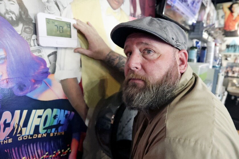 """In this Wednesday, Sept. 25, 2019 photo, George Johnson points to a thermostat at the barber shop where he works in Longwood, Fla. Johnson says he rarely uses public transportation but is worried about climate change and keeps his driving to a minimum. He sometimes takes other conservation steps such as eating vegetarian meals and planting trees while always turning off unnecessary lights. """"You've got to start somewhere,"""" he said. """"If everybody just turned off their lights one hour or anything, it can help."""" (AP Photo/John Raoux)"""