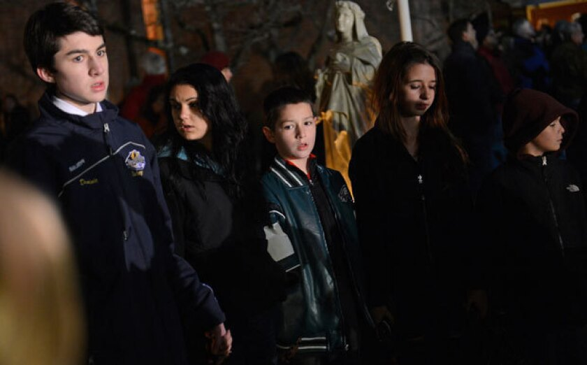 People gather for a prayer vigil at St. Rose Church in Newtown, Conn., on Friday evening.