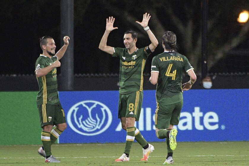The Portland Timbers' Diego Valeri, middle, celebrates his goal with Sebastian Blanco, left, and Jorge Villafana.