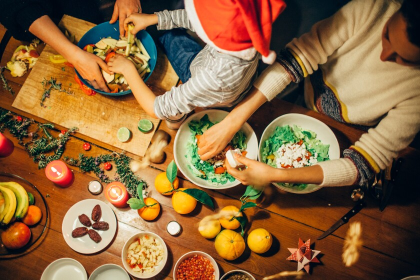 Two adults and a child work on holiday dishes spread across a table.