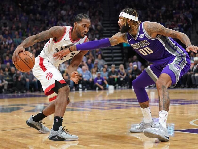 El pívot Willie Cauley-Stein (d) de Sacramento Kings en acción ante el alero Kawhi Leonard (i) de Toronto Raptors, durante un juego de la NBA entre Sacramento Kings y Toronto Raptors, en el Golden 1 Center de Sacramento, California (EE. UU.). EFE