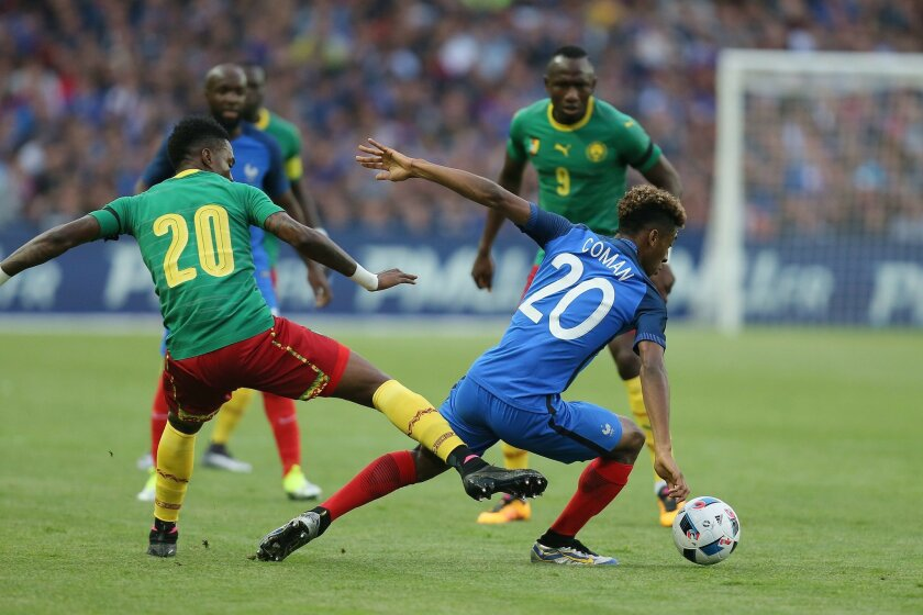 France's Kingsley Coman, right, challenges for the ball with Cameroon's Georges Mandjeck during a friendly soccer match between France and Cameroon at the La Beaujoire Stadium in Nantes, western France, Monday, May 30, 2016. The French squad is in preparation for the EURO 2016 soccer championships