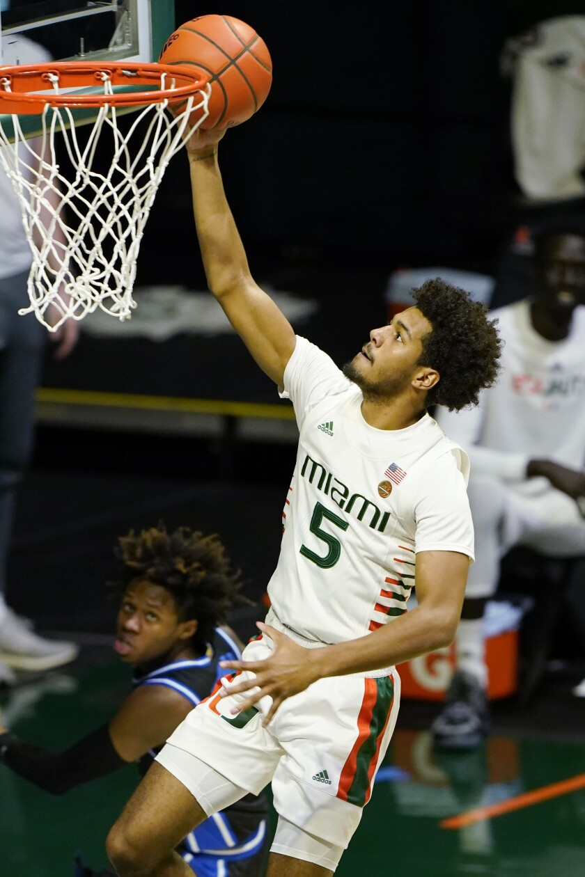 Miami guard Harlond Beverly (5) dunks the ball over Duke guard DJ Steward during the second half of an NCAA college basketball game, Monday, Feb. 1, 2021, in Coral Gables, Fla. Miami defeated Duke 77-75. (AP Photo/Marta Lavandier)