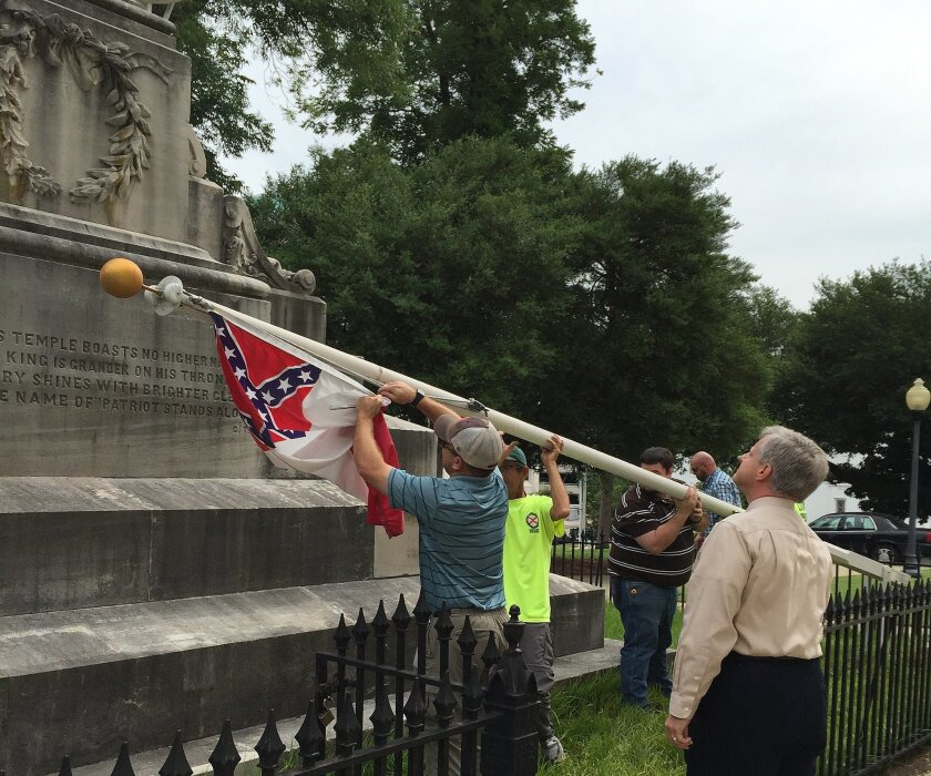 In this 2015 file photo, state workers take down a Confederate national flag on the grounds of the Alabama State Capitol.