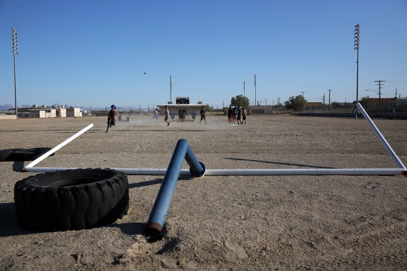 The Trona High football team practices at their school in Trona, Calif. A goal post was knocked to the ground after two earthquakes hit in July near Ridgecrest.