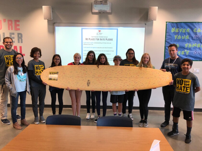 Earl Warren students signed a surfboard as part of a pledge to bring the No Place for Hate campaign to campus.