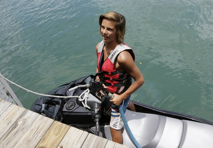 Caden Key, 14, of Jupiter, Fla., talks with the news media after fueling his jet ski at the JIB Club Marina, Tuesday, July 28, 2015, in Tequesta, Fla. Key knew of the two Florida teens who've been missing since Friday, July 24, who were last seen fueling their boat at this marina before heading out to fish. The search continues for the boys, from the Atlantic waters off Daytona Beach, Fla., north through Savannah, Ga. (AP Photo/Lynne Sladky)