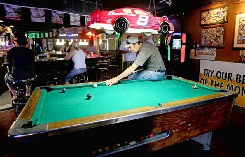 Daniel Scellato plays a round of pool at a local dive bar, The Helm, in Costa Mesa.