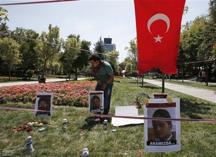 A man tends a makeshift memorial for the victims of clashes between protesters and riot police at the Gezi Park in Istanbul, Turkey, Friday, July 12, 2013. Five people died during the nationwide anti-government protests that hit Turkey in June. The sign under the victims' photographs reads ''He is between us.'' (AP Photo/Thanassis Stavrakis)