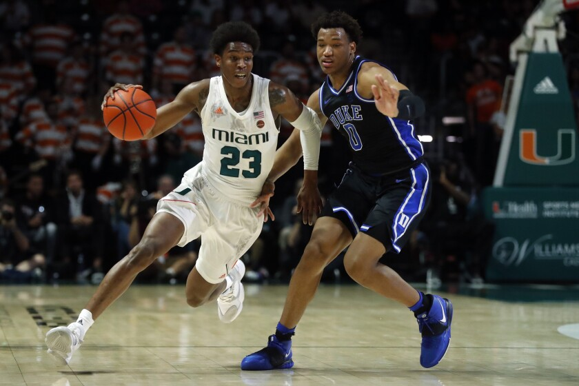 Miami guard Kameron McGusty (23) drives past Duke forward Wendell Moore Jr. (0) during the first half of an NCAA college basketball game, Saturday, Jan. 4, 2020, in Coral Gables, Fla. (AP Photo/Wilfredo Lee)