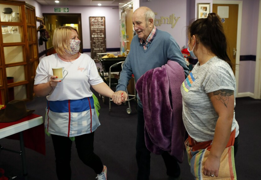 Nurses guide a resident at Wren Hall nursing home this week in the village of Selston, in central England.