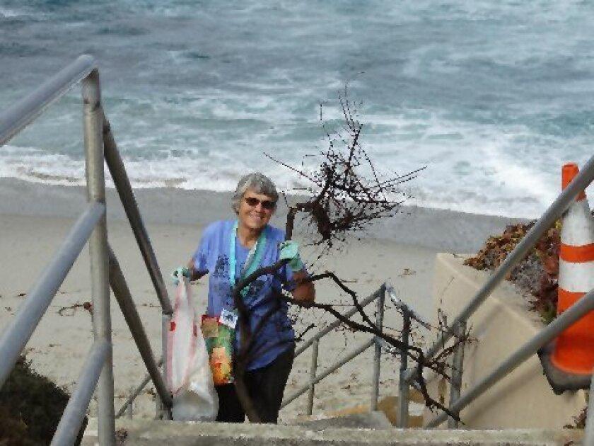 Ellen Shively removes debris from South Casa beach in La Jolla.