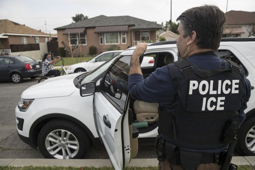 An ICE officer stands outside the home of a 47-year-old Mexican national in Montebello on April 18, 2017.