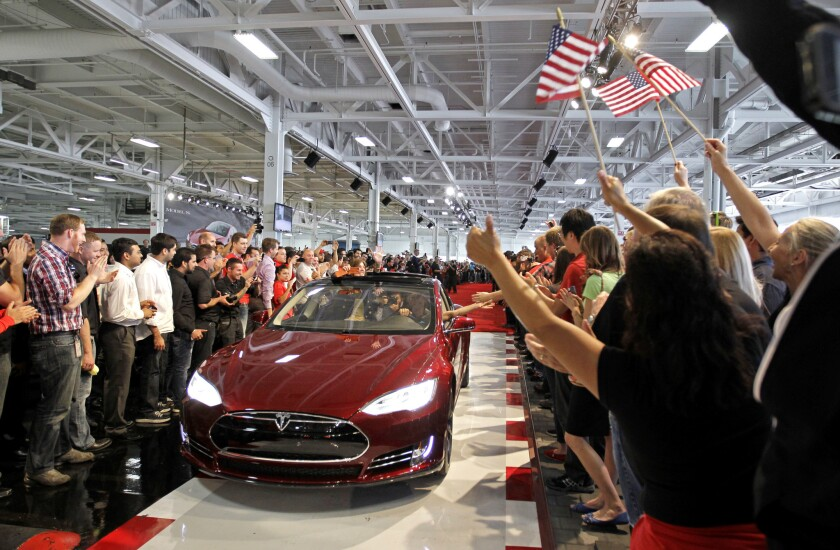 Tesla workers cheer on one the first Tesla Model S cars sold during a rally at the Tesla factory in Fremont, Calif, on June 22, 2012.