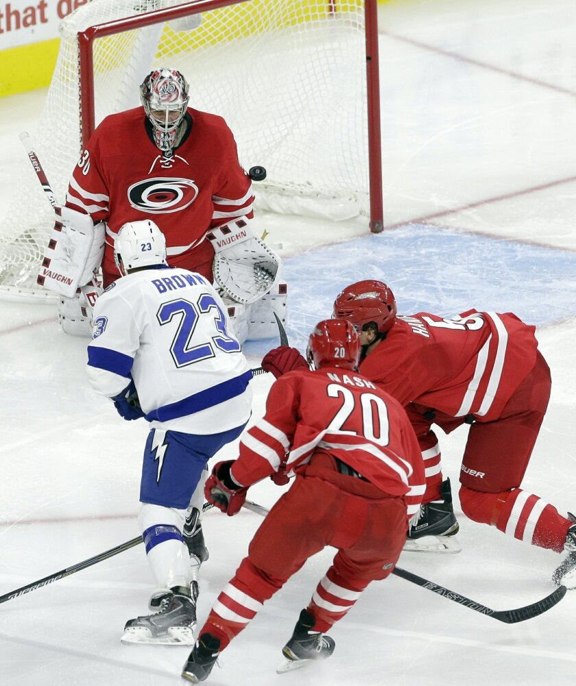 Tampa Bay Lightning's J.T. Brown (23) scores on Carolina Hurricanes goalie Cam Ward as Hurricanes' Riley Nash (20) and Noah Hanifin defend during the third period of an NHL hockey game in Raleigh, N.C., Sunday, Nov. 1, 2015. Tampa Bay won 4-3. (AP Photo/Gerry Broome)