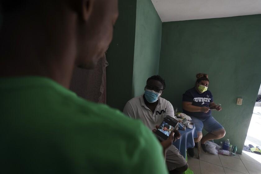 Mensah Montant, centro, y su esposa Virginia Salazar visitan a un migrante haitiano