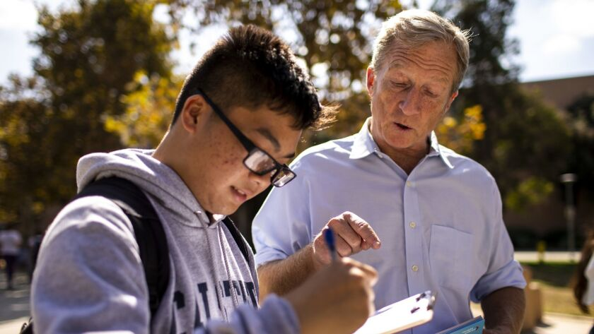 Tom Steyer helps Kevin Huy Nguyen, 18, fill out paperwork to register to vote at Cal State Fullerton. Steyer's advocacy group, NextGen America, is spending $33 million on youth voter outreach this year.