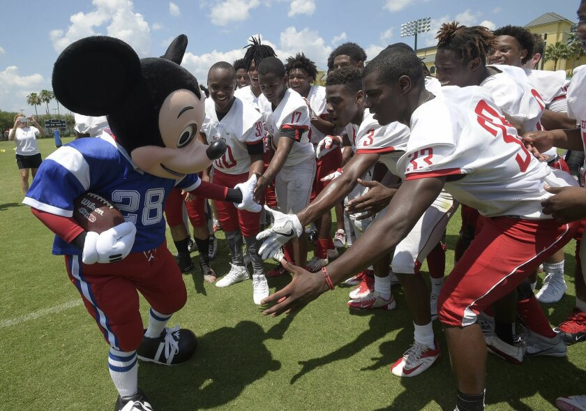 An actor dressed as Mickey Mouse, left, slaps hands with members of the Edgewater High School football team before a news conference announcing Orlando, Fla., as the new host for the NFL Pro Bowl football game Wednesday, June 1, 2016, in Kissimmee, Fla. (AP Photo/Phelan M. Ebenhack)
