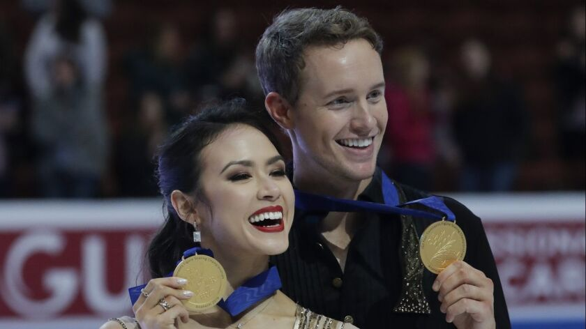Madison Chock and Evan Bates show off their gold medals after winning the ice dancing competition at the Four Continents Figure Skating Championships at the Honda Center on Sunday.