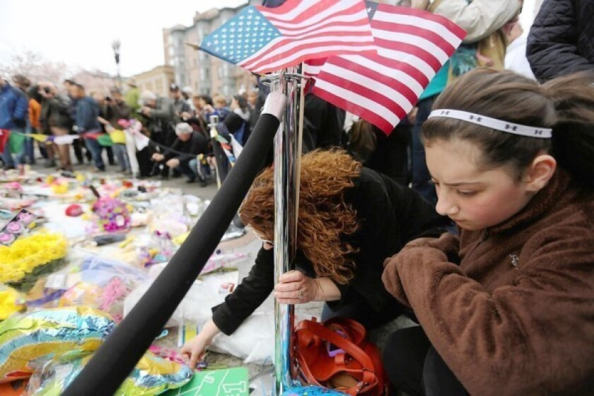 People gather at a makeshift memorial for victims near the site of the Boston Marathon bombing. With one suspect dead and the other captured, the city celebrated as best it could -- including a boisterous resumption of baseball at Fenway Park.