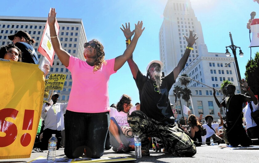 Demonstrators drop to their knees during a march in downtown L.A. in August.