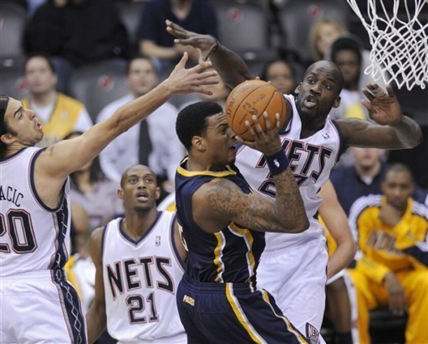 Indiana Pacers' Brandon Rush attempts to shoot as he is pressured by New Jersey Nets' Johan Petro, right, of France, and Sasha Vujacic, left, of Slovenia, during the second quarter of an NBA basketball game Monday, March 21, 2011 in Newark, N.J. (AP Photo/Bill Kostroun)
