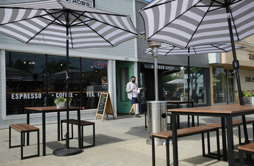 With coffee in hand, Frank Aguirre walks out to outdoor seating at Rob's Brewpoint on Main Street in El Cajon.