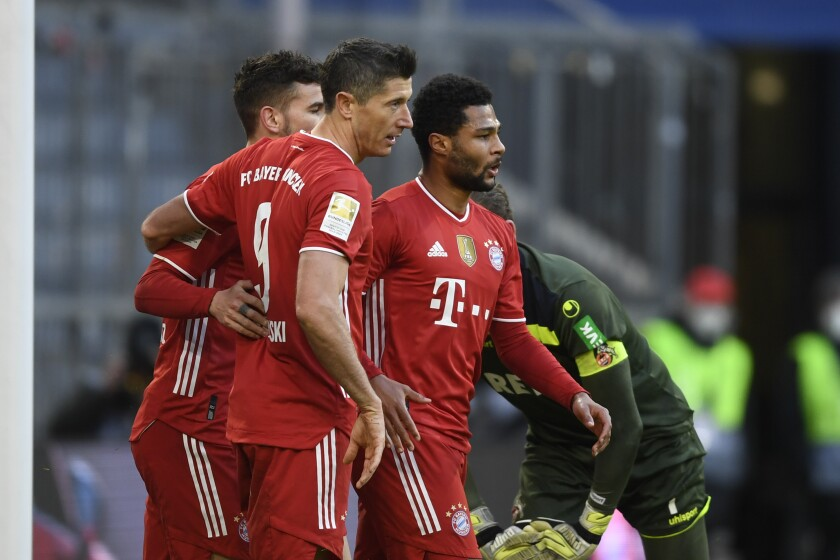 Bayern's Lucas Hernandez, left,, Robert Lewandowski, center, and Serge Gnabry celebrate after a goal during a German Bundesliga soccer match between Bayern Munich and 1.FC Cologne in Munich, Germany, Saturday, Feb. 27, 2021. (AP Photo/Andreas Schaad)