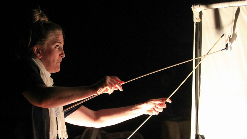Director Samantha Ginn creates shadow effects from the back side of a screen during a dress rehearsa