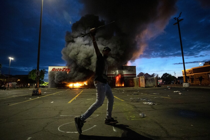 A protester near a burning store in Minneapolis on Wednesday night.