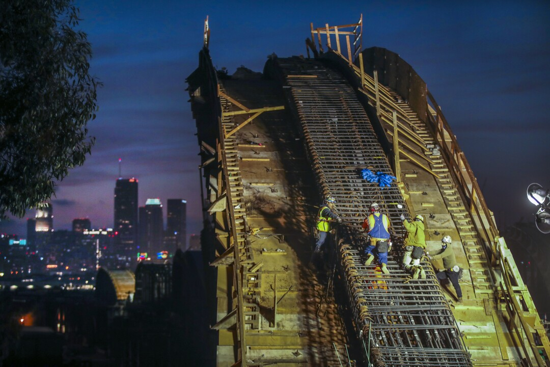 The downtown skyline begins to glow in the distance as work continues at sunset