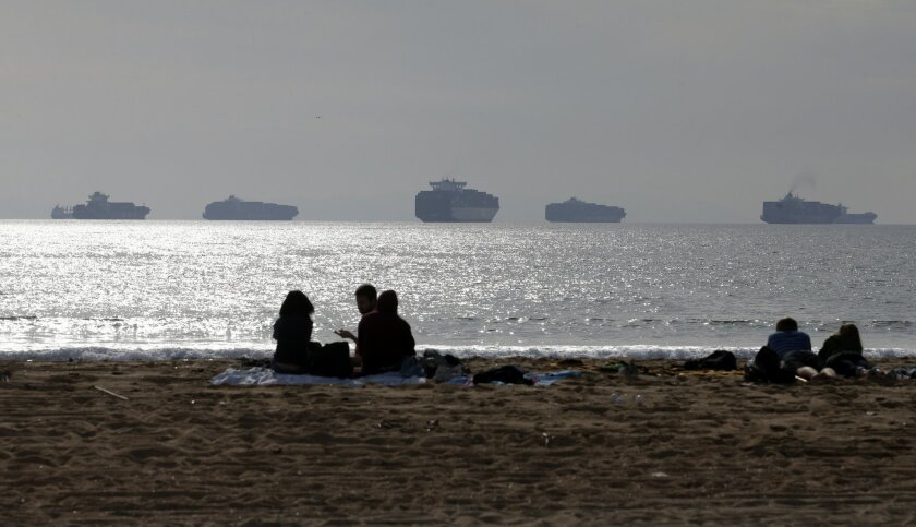 FILE - In this Feb. 20, 2015 file photo, people sit on the sand in Sunset Beach, Calif., as loaded cargo ships are anchored outside the Ports of Long Beach and Los Angeles. A tentative contract agreement that restored the flow of international trade through West Coast seaports earlier this year took a big step closer to becoming official, Friday, April 3, 2015 as representatives of the dockworkers' union overwhelmingly recommended that rank-and-file members vote to approve the deal. Difficult contract negotiations nearly closed 29 seaports from San Diego to Seattle, causing major delays in the delivery of billions of dollars of imports and exports. (AP Photo/Jae C. Hong, File)