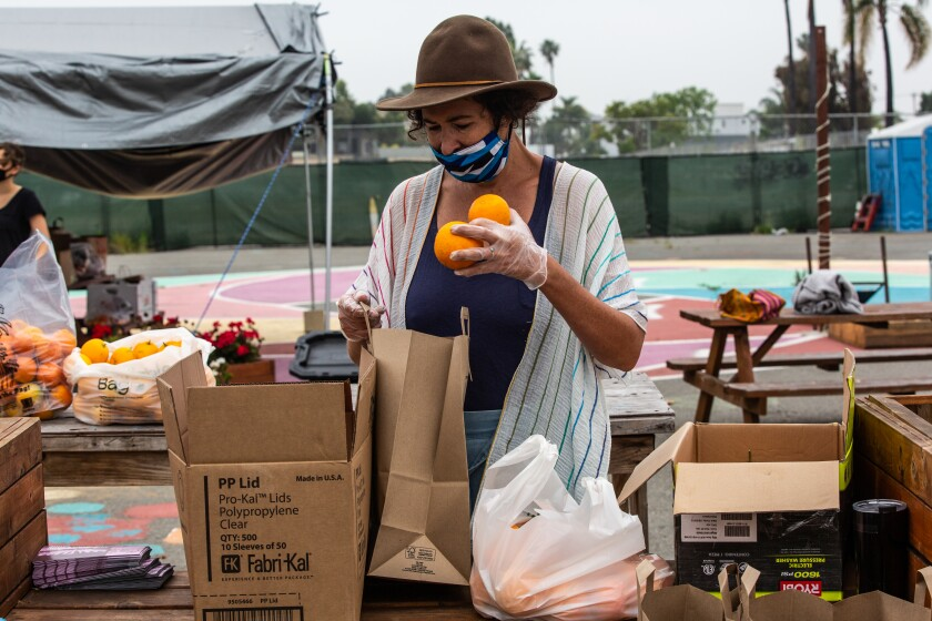Beryl Forman sorts and bags donated fruit in City Heights to hand out to residents in need at a fruit swap Wednesday.