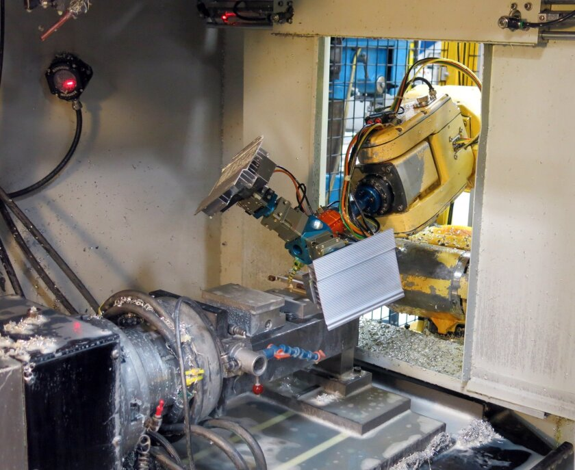 A robot loads a part into a milling machine at Alexandria Industries in Alexandria, Minn., on April 9. Skilled workers no longer need to load the machine.