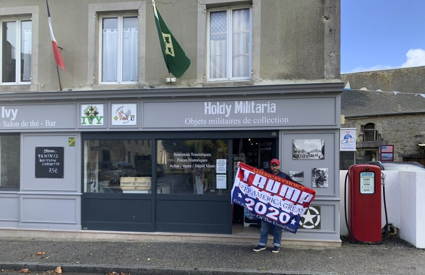 Philippe Tanne, of France, holds a Trump 2020 flag outside the military memorabilia store he runs in the Normandy town of Sainte-Marie-du-Mont, one of the sites of D-Day invasion in 1944, Tuesday, Nov. 3, 2020. Tanne, a French former soldier who hopes Trump wins reelection, is among the multitudes of people across the globe for whom the U.S. election is not a far-away happening in a far-away land but an impossible-to-ignore big deal for the planet. (Courtesy of Philippe Tanne via AP)
