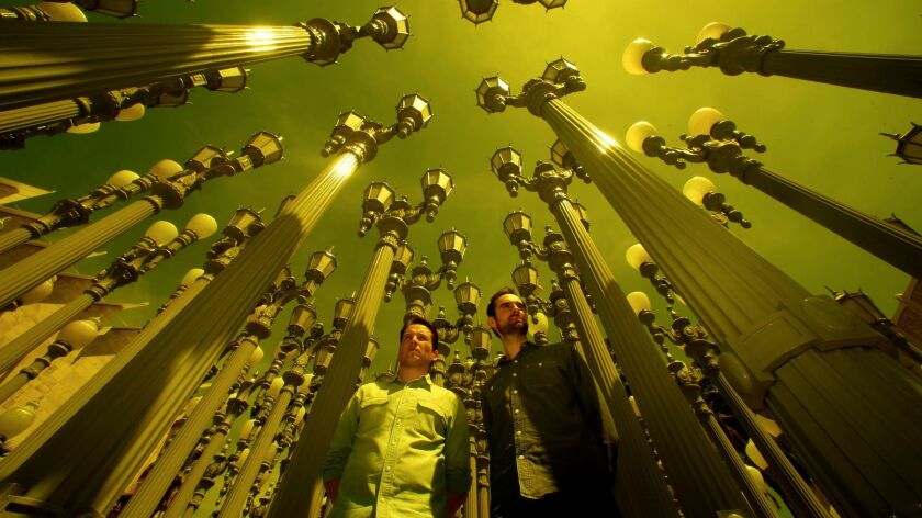 "Richard Dewey, left, and Timothy Marrinan, the directors of a new documentary about the late Los Angeles artist Chris Burden, stand amid his sculpture ""Urban Light"" at LACMA."