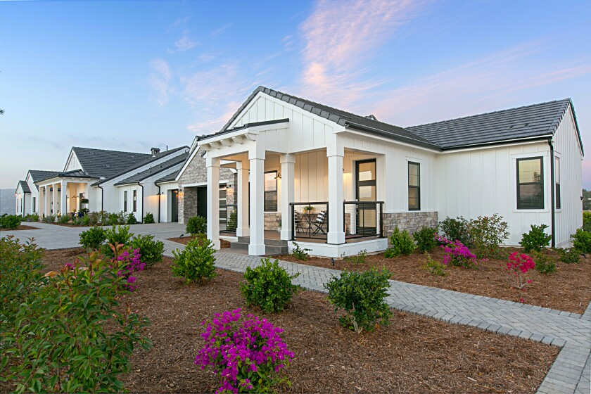 White clapboard siding adds farmhouse style to the front elevation of MDD's new urban ranch home, as seen on the attached 1,200-square-foot guest house with its own porch.