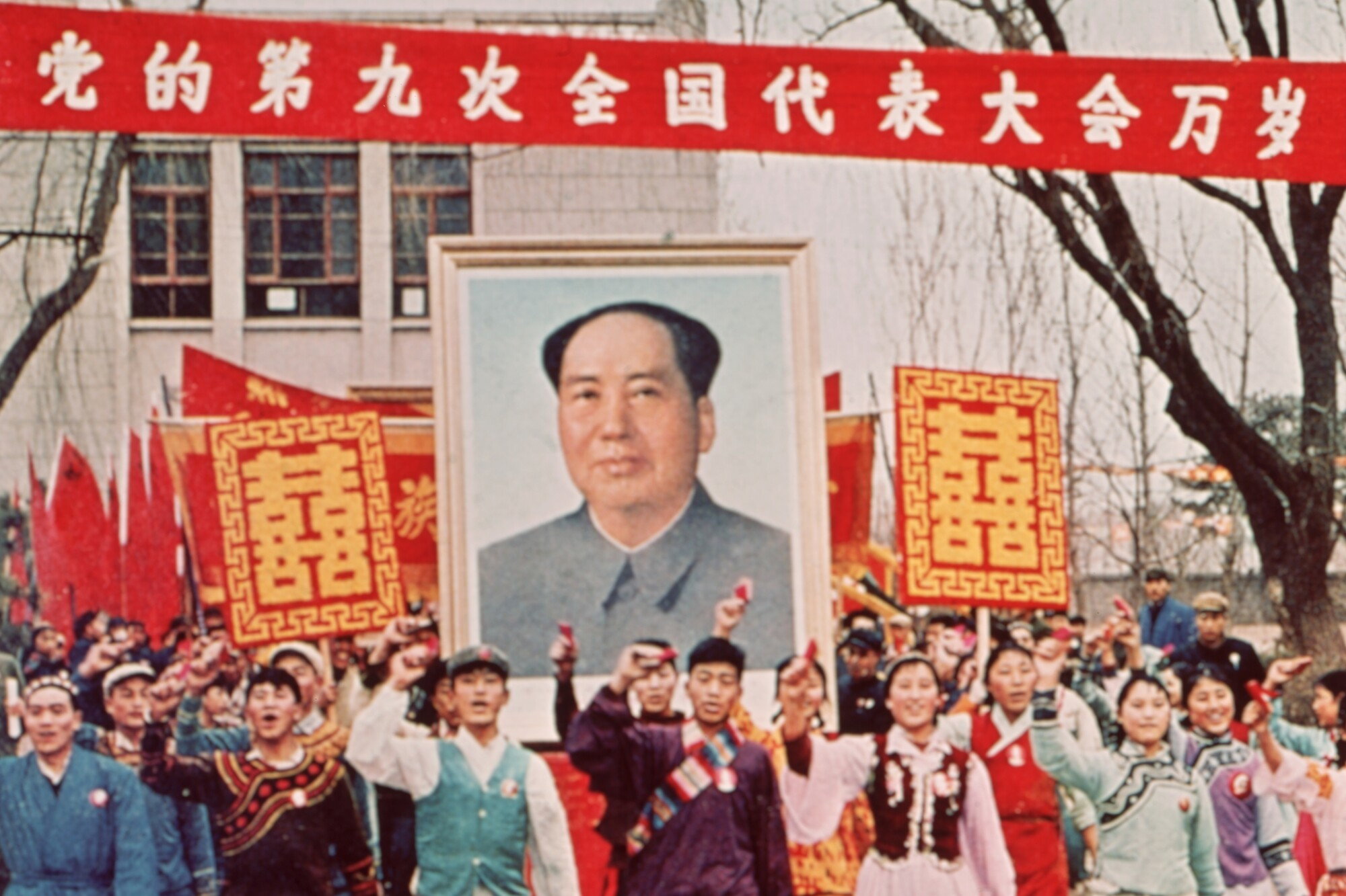People march  carrying a large poster of Chairman Mao Zedong during the Cultural Revolution in China in 1968.