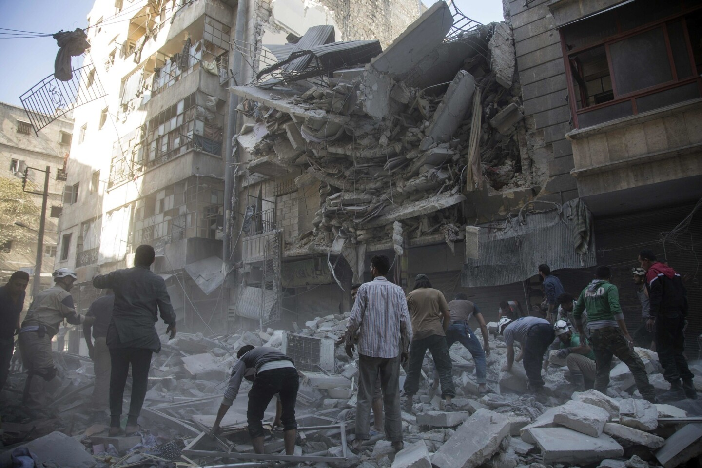Syrian civilians gather after government airstrikes in the rebel-held Shaar neighborhood of Aleppo.