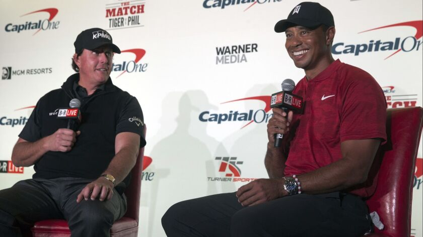 Phil Mickelson, left, and Tiger Woods speak during a news conference at Shadow Creek Golf Course in