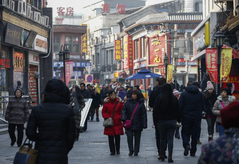 People stroll in the shopping area of Qianmen district in Beijing on Tuesday.