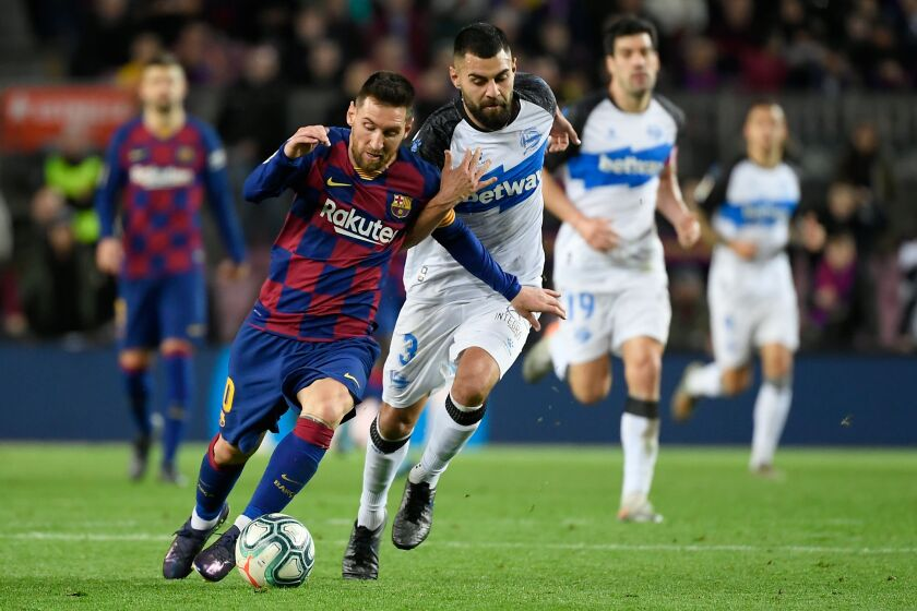 Barcelona forward Lionel Messi, left, vies for the ball with Alaves defender Ruben Duarte