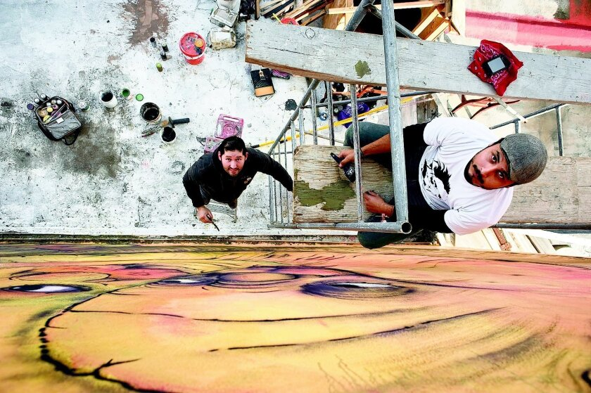 """Tijuana mural artists Alonso Delgadillo, 29, center, and David """"M,"""" 27, right, pose for a photograph, while painting a mural on the side of friend's house on February 10, 2013 in Tijuana, Mexico. David """"M"""" uses the letter """"M"""" as his last name. Photo - David Maung"""
