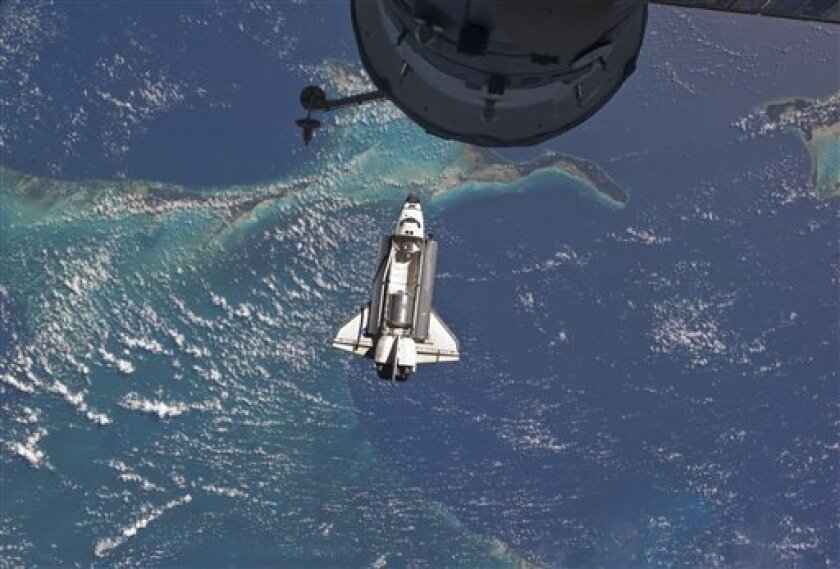 In this Sunday, July 10, 2011 photo provided by NASA, the space shuttle Atlantis is seen over the Bahamas prior to a perfect docking with the International Space Station. Part of a Russian Progress spacecraft which is docked to the station is in the foreground. (AP Photo/NASA)